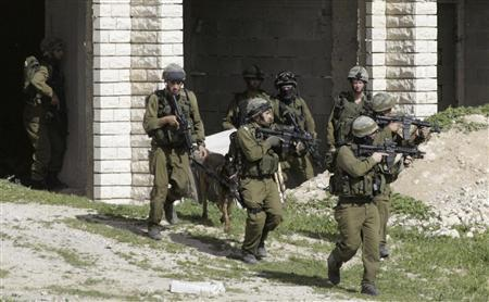 Israeli soldiers move into position during an army raid in the West Bank village of Obadiyah, near Bethlehem, as they search for wanted Palestinian militants, March 21, 2007. REUTERS/Nayef Hashlamoun