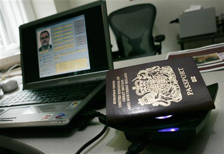 A file photo of a biometric passport is shown atop a special reader connected to a computer that can read the passport holders personal information, October 24, 2005. An estimated 10,000 passports were issued to fraudulent applicants in the year to last September, the Home Office said on Wednesday as it launched a new initiative to reduce identity fraud. REUTERS/Jason Reed