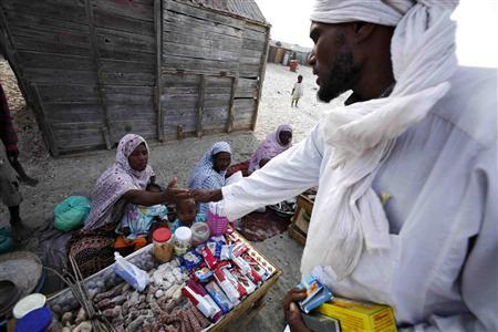 A Mauritanian man buys goods in the Keube slum in the capital Nouakchott in this March 13, 2007 picture. Herding camels or goats out in the sun-blasted dunes of the Sahara, or serving hot mint tea to guests in the richly carpeted villas of Nouakchott, Mauritanian slaves serve their masters and are passed on as family chattels from generation to generation. REUTERS/Finbarr O'Reilly
