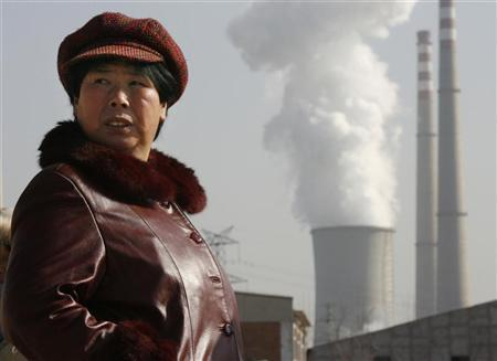 A woman walks near a power plant's cooling tower and smoke stacks on the outskirts of Beijing February 1, 2007. China is on course to overtake the United States this year as the world's biggest carbon emitter, estimates based on Chinese energy data show, potentially pressuring Beijing to take more action on climate change. REUTERS/Claro Cortes IV