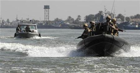 British Royal Marines ride in a patrol boat as an Iraqi Coast Guard patrol boat is seen nearby south of Baghdad, February 15, 2007. Iran said on Sunday it was considering charging 15 British sailors and marines with illegally entering its waters, but added it may give consular access to them after an investigation. REUTERS/British Royal Marines/Crown Copyright/Handout
