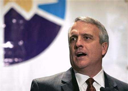 Colorado Governor Bill Ritter stands in front of the logo for the 2008 Denver Democratic National Convention at a news conference reacting to the cities selection in Denver, in this January 11, 2007 file photo. Colorado utilities will have to get 20 percent of their electricity supply from renewable energies by 2020 under a bill signed into law on Tuesday by Gov. Ritter. REUTERS/Rick Wilking