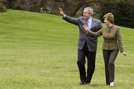 President Bush and first lady Laura Bush wave to visitors as they return from a visit at Camp David to the White House, April 1, 2007. REUTERS/Jonathan Ernst