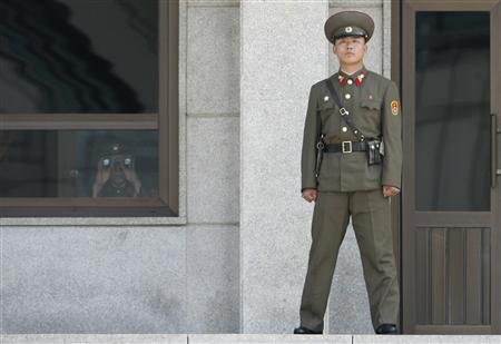 A North Korean soldier looks south through a pair of binoculars while a comrade stands guard at the truce village of Panmunjom, in the demilitarised zone separating the two Koreas, about 34 miles north of Seoul, April 4, 2007. REUTERS/Jo Yong-Hak