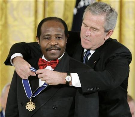 President George W. Bush (R) presents his Presidential Medal of Freedom to Paul Rusesabagina, who sheltered people at a hotel he managed during the 1994 Rwandan genocide, at a ceremony in the East Room of the White House in Washington November 9, 2005. To much of the outside world, Paul Rusesabagina is a hero who saved 1,200 people from genocide in events depicted in the Oscar-nominated film ''Hotel Rwanda''. But as the genocide's 13th anniversary approaches in his native Rwanda, a bitter row has erupted between Rusesabagina and critics, including President Paul Kagame, who say he is profiting from the victims' misery and rewriting Rwanda's history for his own gain. REUTERS/Jason Reed