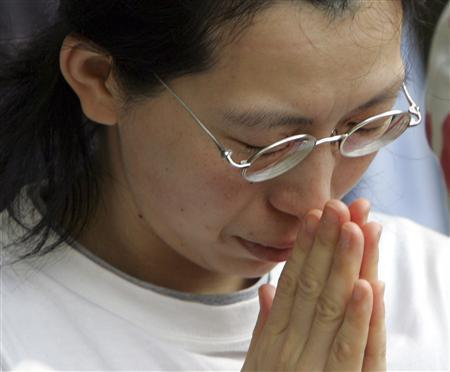 A visitor mourns the victims of the Battle of Okinawa at Himeyuri Peace Memorial monument in Itoman on the southern Japanese island of Okinawa March 28, 2006. The fighting on Zamami, south of the main Okinawan island, was the prelude to three months of carnage that took some 200,000 lives, about half of them Okinawan men, women and children. Many civilians, often entire families, committed suicide rather than surrender to Americans, by some accounts on the orders of fanatical Japanese soldiers. Picture taken March 28, 2006. REUTERS/Issei Kato