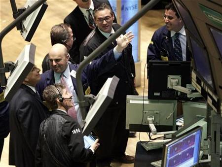 A trader smiles while pointing to a monitor on the floor of the New York Stock Exchange in New York April 3, 2007. REUTERS/Shannon Stapleton