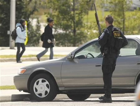 Police officer Skip Vaughn guards the perimeter of the Virginia Tech campus as students evacuate after a gunman shot dozens of people on the university campus in Blacksburg, Virginia, in this April 16, 2007 file photo. The Virginia Tech killings have set off calls for tighter U.S. gun laws but anyone wanting to know why those demands likely will make little headway should visit Kennesaw, a town where owning a gun is both popular and mandatory. REUTERS/Brendan Bush