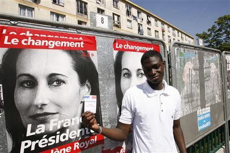 Mendy Beuteco, a French youth, from the Paris suburb of Clichy-sous-Bois, displays his voter registration card as he stands near election posters for Socialist candidate Segolene Royal, who he voted for in the first round of the presidential elections, April 22, 2007. REUTERS/Victor Tonelli