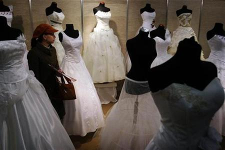 A woman walks among bridal dresses during the opening of a three-day wedding fair in Bucharest, in this March 23, 2007 file photo. Almost half of Britain's divorcing couples used a private investigator last year to confirm, or deny, their suspicions about their spouse cheating on them, accountancy firm Grant Thornton said on Monday. REUTERS/Mihai Barbu