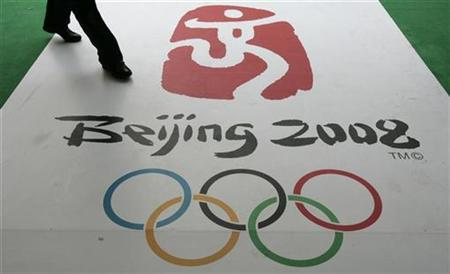 A man walks past the official logo for the 2008 Beijing Olympics during a countdown ceremony in Hong Kong, in this March 27, 2007 file photo. Beijing's meteorological bureau believes it can manipulate the weather to guarantee a dry opening ceremony at next year's Olympic Games, an official said on Wednesday. REUTERS/Bobby Yip