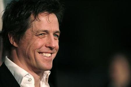 Cast member Hugh Grant smiles at the world premiere of ''Music and Lyrics'' at the Grauman's Chinese theatre in Hollywood, California, in this February 7, 2007 file photo. Grant has been arrested and questioned by police after a photographer accused the actor of attacking him with a tub of baked beans. REUTERS/Mario Anzuoni
