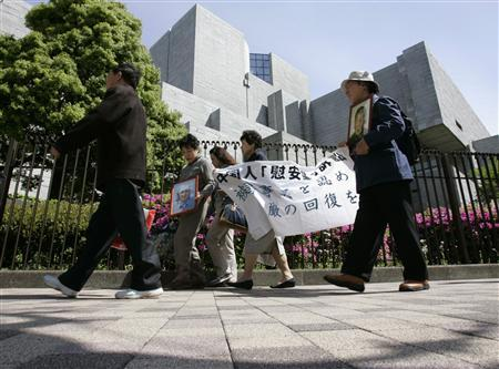Supporters of plaintiffs hold a banner and portraits of Chinese plaintiff Hou Qiaolian (L) and Guo Xicui as they walk into the Supreme Court in Tokyo, April 27, 2007. REUTERS/Toru Hanai