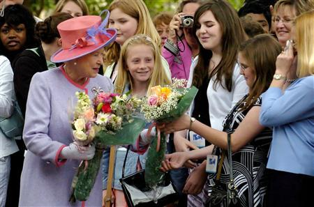 Queen Elizabeth is presented with flowers as takes part in a walkabout as she arrives at the Governor's Mansion in Richmond, Virginia, May 3, 2007. When in the presence of Britain's Queen Elizabeth, Americans are not expected to bow but should not shake her hand until the queen extends her hand. REUTERS/Mike Theiler/Pool