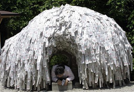 A woman crawls out of a wish tunnel at Yasui Konpiragu Shrine in Kyoto, west of Tokyo May 7, 2007. REUTERS/Kim Kyung-Hoon