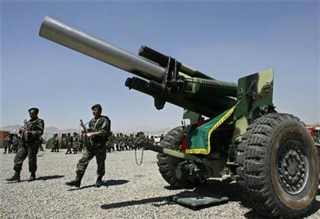Afghan soldiers walk by a 155mm Howitzer artillery, during a ceremony in Kabul, May 9, 2007. REUTERS/Ahmad Masood