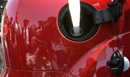 The faces of people are reflected on a hybrid vehicle that runs on petrol mixed with ethanol made from rice as the vehicle is refuelled with ethanol near a small test plant in Shinanomachi, central Japan May 11, 2007. Japanese motorists may one day pump their cars full of sake, the fermented rice wine that is Japan's national drink, under a government-funded project unveiled in a snow-capped mountain resort on Friday. REUTERS/Toru Hanai
