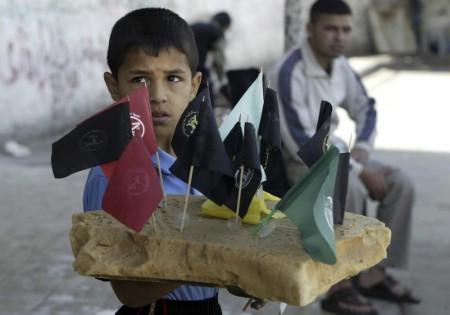 A boy sells flags of Palestinian factions in the street of southern Gaza strip May 14, 2007. A growing number of Palestinian children are roaming the streets of Gaza looking for a meagre wage to help support their families in the impoverished territory. REUTERS/Ibraheem Abu Mustafa (GAZA)