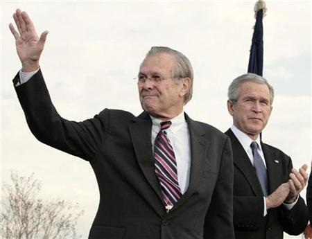 Former Secretary of Defense Donald Rumsfeld waves next to President Bush during the Armed Forces Full Honor Review in Honor of the Secretary of Defense at the Pentagon in Washington, December 15, 2006. The Bush administration is keeping a tight hold on Rumsfeld's resignation letter nearly five months after the former defense secretary and Iraq war manager stepped down. REUTERS/Larry Downing