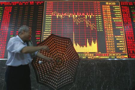 A man closes his umbrella in front of an electronic board at a stock exchange in Wuhan, the capital of central China's Hubei province, May 15, 2007. REUTERS/Stringer
