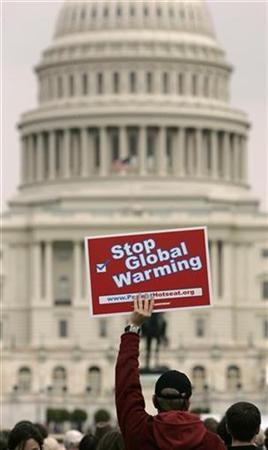 A protester holds up a placard during a Climate Change Protest in front of the U.S. Capitol in Washington, April 14, 2007. A meeting of rich nations next month in Germany will be a ''litmus test'' of how the United States plans to help the world fight climate change, the head of the U.N. Environment Programme (UNEP) said on Tuesday. REUTERS/Hyungwon Kang