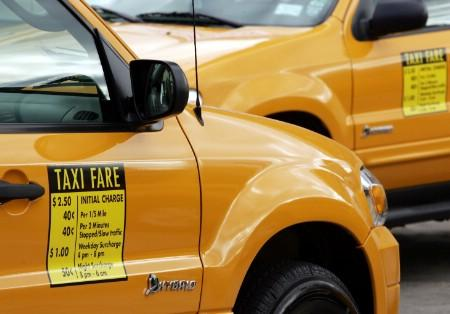 Ford Escape Hybrid taxi cabs are parked together at an event to introduce the fuel-efficient vehicles into the taxi fleet in New York City November 10, 2005. REUTERS/Mike Segar