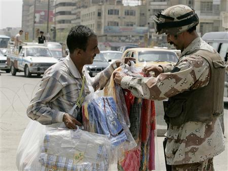 An Iraqi soldier buys children's clothing from a vendor passing a checkpoint in Baghdad, May 23, 2007. REUTERS/Namir Noor-Eldeen
