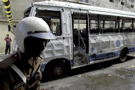 A policeman walks near the wreckage of a military bus in Colombo, May 24 2007. REUTERS/Buddhika Weerasinghe