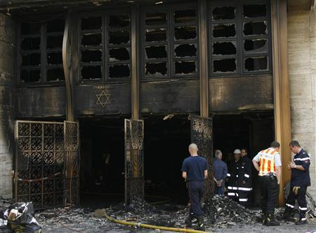 Firemen and policemen at Geneva's Hekhal Haness synagogue, destroyed by fire early May 24, 2007. Switzerland's reputation as a haven of tolerance for immigrants has been undermined in recent weeks by calls for a ban on new minarets, a mysterious synagogue blaze and neo-Nazi threats to disrupt national day celebrations. REUTERS/Denis Balibouse