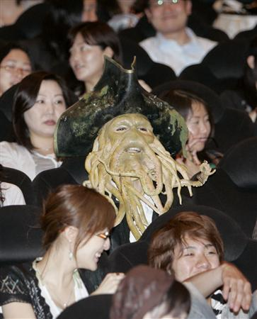 A man dressed as 'Davy Jones', a character from ''Pirates of the Caribbean: At World's End'', sits down to watch the movie at a special premiere in Tokyo May 24, 2007. Malaysian cinemas have found a powerful new weapon in their fight against movie pirates -- military-style night-vision goggles. REUTERS/Kim Kyung-Hoon
