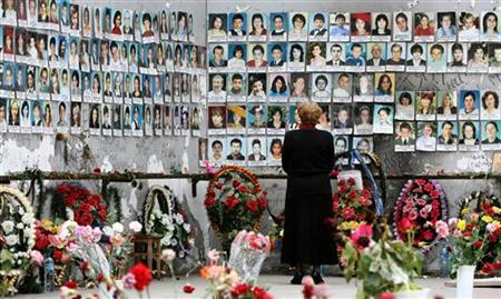 A woman grieves at the wall filled with photographs of the siege victims at school N1 in the town of Beslan, May 18, 2006. A Russian court granted an amnesty to three policemen who were charged with negligence for failing to prevent the 2004 Beslan school massacre, in which 331 people died. REUTERS/Eduard Korniyenko