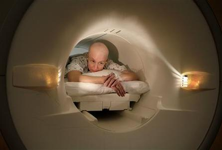 Cancer patient Deborah Charles lies inside the tube of a magnetic resonance imaging scanner during an MRI examination of her breasts at Georgetown University Hospital in Washington May 23, 2007. Like many cancer patients, Charles now spends many of her days going for many medical appointments, treatments and examinations. REUTERS/Jim Bourg