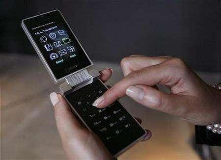 A hostess holds a Porsche Design Mobile Phone in Essen, Germany, June 4, 2007. Audience measurement firm Nielsen said on Wednesday it will begin tracking media consumption over cell phones under a new service called Nielsen Wireless. REUTERS/Ina Fassbender