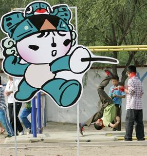 A student turns a somersault near one of the mascots for the 2008 Beijing Olympic games at an Olympic education model school in Miyun County of Beijing June 8, 2007 file photo. What do the conflict in Darfur, forced evictions, media freedoms and the rights of migrant laborers have in common? The answer is China and the 2008 Olympics. REUTERS/Jason Lee