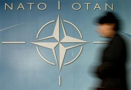 A woman walks past the NATO logo at the entrance of the Alliance headquarters in Brussels, Belgium, December 4, 2003. NATO defense ministers agreed on Thursday that fast action was needed to tackle the threat of ''cyber attacks'' on key Internet sites after Estonia suffered a wave of assaults on its computer networks last month. REUTERS/Thierry Roge