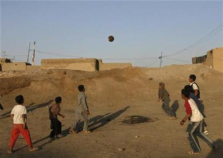Afghan boys play football in the old part of City in Kabul, June 12,2007. At least seven children were killed in a U.S.-led coalition air strike on a religious school in Afghanistan, the coalition said on Monday, amid rising anger over civilian deaths from foreign military operations. REUTERS/Omar Sobhani