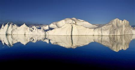 An iceberg is reflected in calm ocean water at the mouth of the Jakobshavns ice fjord near Ilulissat in this photo taken May 15, 2007. New research shows that man-made climate change could cause the Greenland ice sheet to break up in hundreds, rather than thousands, of years, the chair of a United Nations panel of scientists said on Monday. REUTERS/Bob Strong