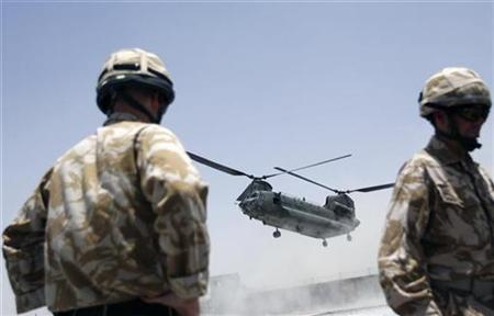 British soldiers watch as a Chinook helicopter lands in Lashkar Gah, capital of the southern Afghan province of Helmand, June 15, 2007. Global warming is such a threat to security that military planners must build it into their calculations, the head of Britain's armed forces said on Monday. REUTERS/Ahmad Masood