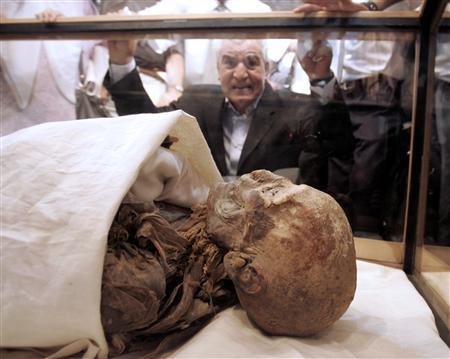 Zahi Hawass, Secretary-General of the Supreme Council of Antiquities, looks at a mummy identified as Queen Hatshepsut before a news conference at the Egyptian museum in Cairo June 27, 2007. Egyptologists think they have identified with certainty the mummy of Hatshepsut, the most famous queen to rule ancient Egypt, found in a humble tomb in the Valley of the Kings, an archaeologist said on Monday. REUTERS/Nasser Nuri