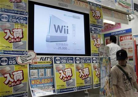 Men walk near a display showing Nintendo's Wii game console at a game shop in Tokyo's Akihabara electronic district, June 25, 2007. Nintendo Co. Ltd.'s Wii outsold Sony Corp.'s PlayStation 3 by a ratio of over 6 to 1 in June in Japan, a game magazine publisher said, solidifying Nintendo's leading position. REUTERS/Toru Hanai