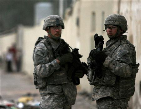 U.S. soldiers from the 2nd battalion, 32nd Field Artillery brigade talk to each other during a night patrol on the streets of Baghdad, July 9, 2007. REUTERS/Nikola Solic