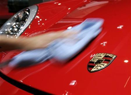 An employee wipes a Porsche 911 Carrera S which is on display at the 76th Geneva motor show in Geneva, Switzerland, February 28, 2006. Malaysian police were left red-faced after a man who abandoned the theft of a $280,000 Porsche for lack of fuel attempted the crime a second time and drove the sportscar out of a police station, local media said. REUTERS/Ruben Sprich