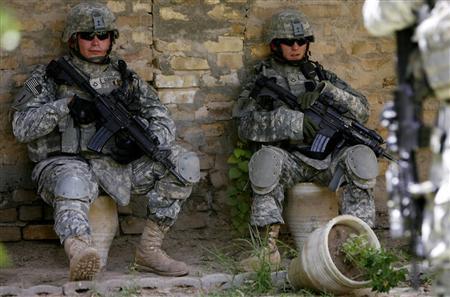 U.S. soldiers rest in between monitoring a mosque in Yarmuk neighbourhood in Baghdad July 20, 2007. REUTERS/Nikola Solic