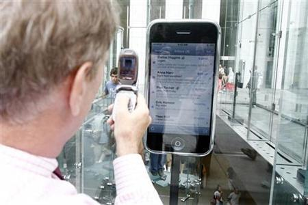 A passer-by takes a cell phone picture of a replica display of Apple's iPhone at the Fifth Avenue Apple store in New York, June 25, 2007. If you were walking along and spotted a cell phone, would you pocket it or try to find its owner? An international survey found people were more honest than expected, with Slovenians leading the pack. REUTERS/Keith Bedford