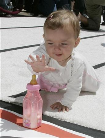 A baby reaches for a bottle at a ''diaper derby'' race at the Sony studios lot in Los Angeles, August 26, 2004. A computer program that learns to decode sounds from different languages in the same way that a baby does helps to shed new light on how people learn to talk, researchers said on Tuesday. REUTERS/Fred Prouser