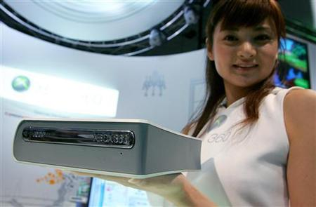 A model holds Microsoft Corp.'s HD DVD player for the Xbox 360 game console during Tokyo Game Show 2006 at Makuhari Messe in Chiba, east of Tokyo September 22, 2006. Microsoft Corp. said on Thursday it would lower the price of the high-definition DVD player accessory in the United States to $179 from $199, and add five free movies to anyone who buys the machine in August or September. REUTERS/Kiyoshi Ota