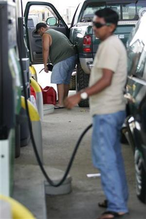 Customers fill up at a gas station in a file photo. Oil rose above $75 a barrel on Friday as investors focused on tightening fuel supplies and brushed off immediate worries over corporate borrowing costs and the U.S. economy that roiled stock markets. REUTERS/Marc Serota