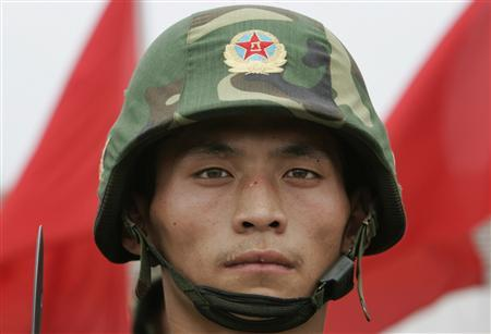 A soldier from the People's Liberation Army Unit 196 stands still during a military demonstration at a base on the outskirts of north China's Tianjin municipality, July 30, 2007. China let in a crack of light on its military modernisation on Monday, opening a camp to foreign reporters to put out the message: we have nothing to hide and you have nothing to fear. REUTERS/Alfred Cheng Jin