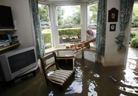 Householder Jeff Clarke recovers furniture from his flooded home in Tewkesbury, central England, July 24, 2007. REUTERS/Darren Staples (BRITAIN)