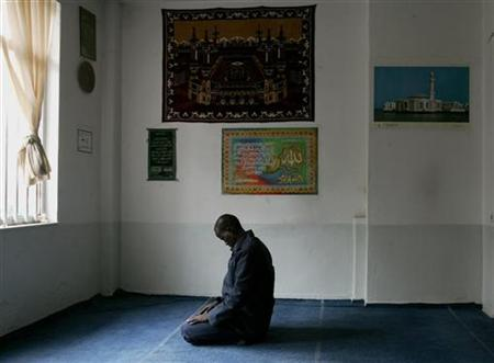 A Muslim living in Athens prays in a small apartment used as a makeshift mosque in this file photo from March 2, 2006. REUTERS/Yiorgos Karahalis